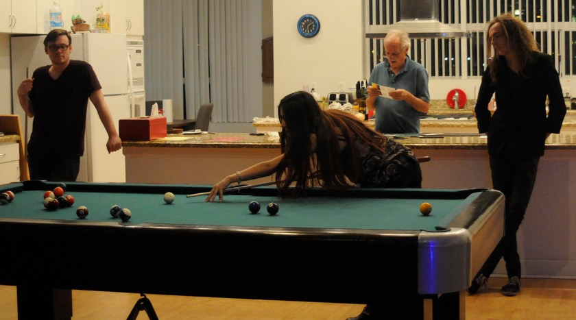 Sasonov (front) sets up her shot for pool while Frasier (far left) and Vallance (far right) watch and Muzio (back) works on Friday, Nov. 15. A deceased friend of Muzio use to live in the house but after he past away, his partner let Muzio and three other artists temporarily live in the house.