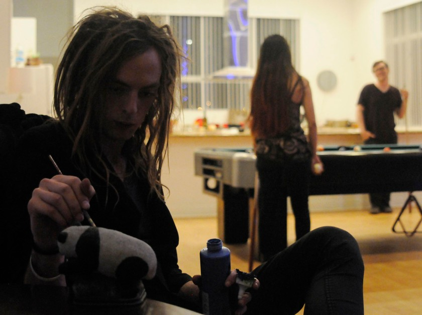 Vallance paints a panda blue while Sasonov (back left) and Frasier (back right) play pool on Friday, Nov. 15. Although it was Third Friday, a less attended art walk in downtown Phoenix, Vallance did not plan to show his art that night because he said typically few people buy work.