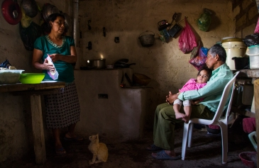 Bertha Maria López cooks in her kitchen with her husband, Juan Luis Alvarado, and granddaughter, Samantha Noely Martínez on March 10, 2015, in Sabana Grande, Nicaragua. The family lives in a rural area without electrification from the country's energy grid. Danika Worthington/JMC 470