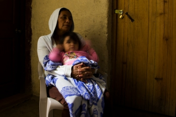 Bertha Maria López holds her granddaughter, Samantha Noely Martínez, under the light in the main passage of her home on the night of March 9, 2015 in Sabana Grande, Nicaragua. When Martínez gets sick during the night, López is able to use the solar-powered lights in her home to find medicine. Danika Worthington/JMC 470