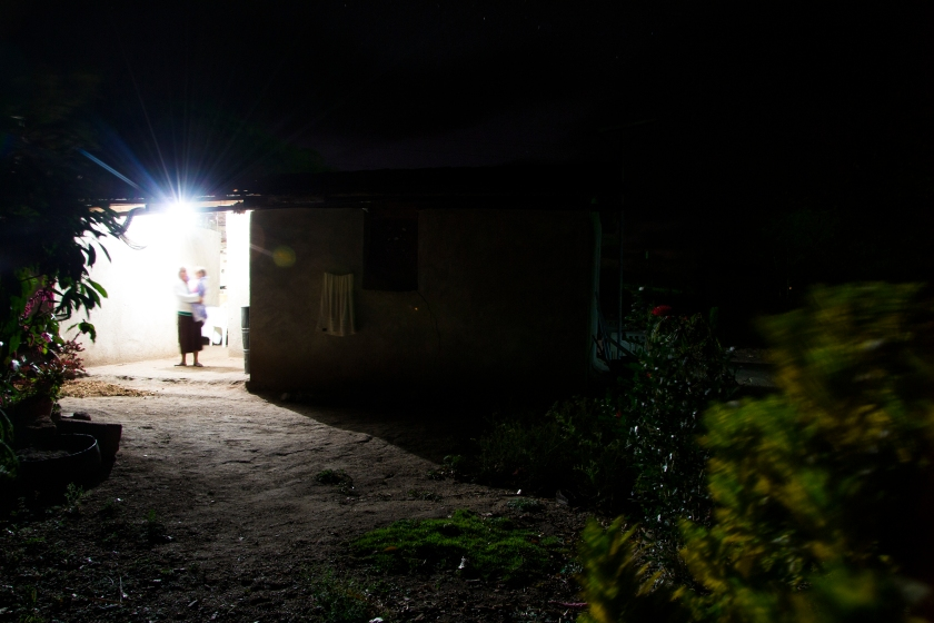 Bertha Maria López and her granddaughter, Samantha Noely Martínez, stand under the light in the walkway to López's house in Sabana Grande, Nicaragua, on March 9, 2015. The family's life has improved with solar power, allowing them to stay up later and do work with more ease. Danika Worthington/JMC 470
