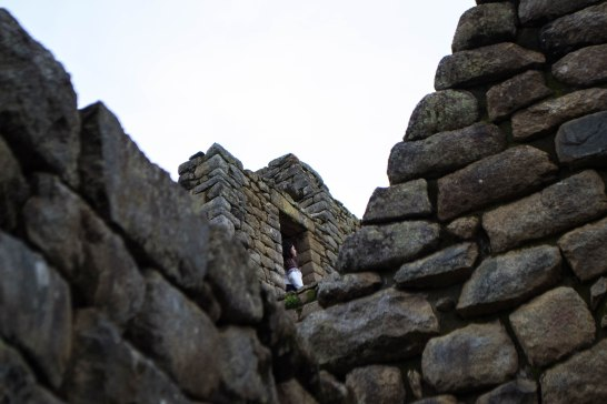 A woman stands in a doorway located in the Incan city of Machu Picchu. The city was hidden from most of the world until the American historian Hiram Bingham stumbled upon it in 1911.