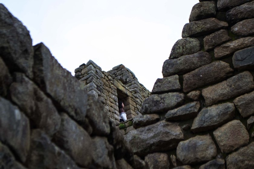A woman stands in the remains of a doorway in Machu Picchu in the Andes Mountains of Peru on Jan. 3, 2015. (Danika Worthington)